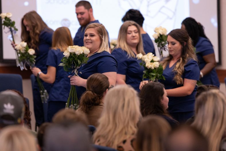 Seminole State College nursing students pass out flowers during the fall 2019 pinning ceremony. The nursing program recently received continued accreditation from the Accreditation Commission for Education in Nursing.