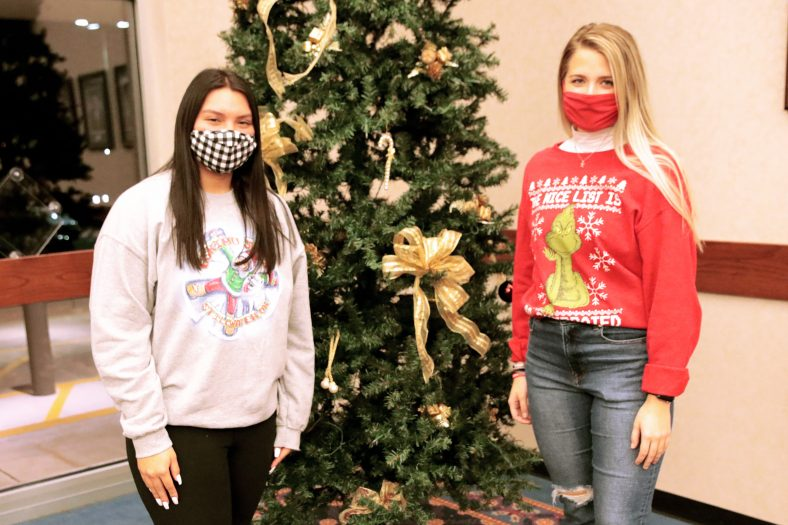 Two students stand by Christmas tree.
