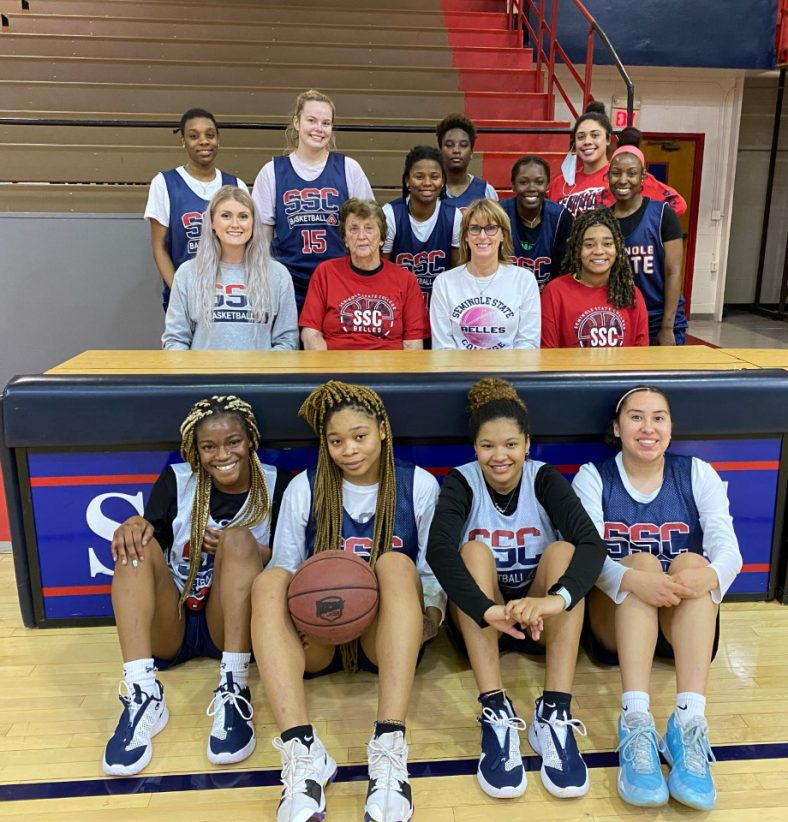 Players and coaching staff of the 2020-2021 Seminole State College Belles basketball team pose for a photo with former Belles Coach Dixie Woodall.