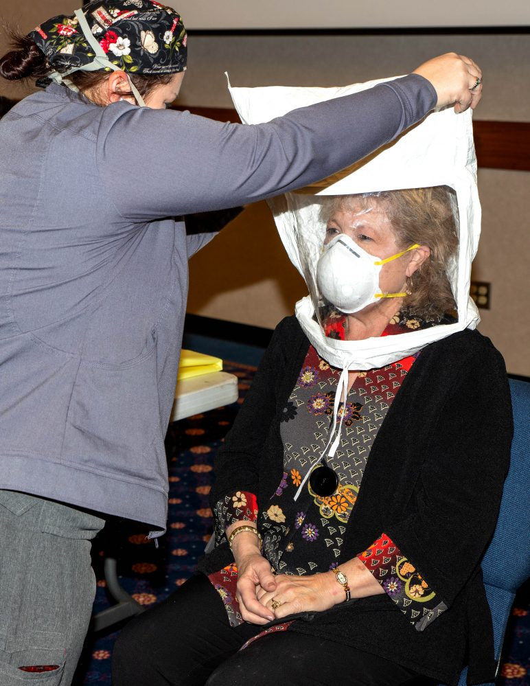 AllianceHealth Respiratory Therapist Candance Moya (left) fits Seminole State College President Lana Reynolds (right) with an N95 mask.