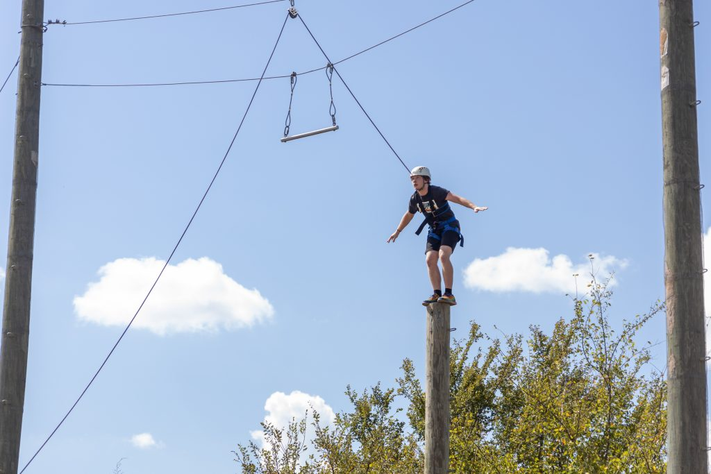 PLC student Frank Bourlon, of Shawnee, leaps from a tall pole to a power jump bar at St. Crispin's Conference Center.