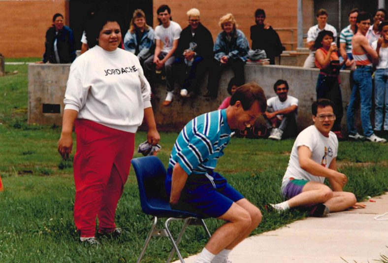 Former counselor Cynthia Yerby looks on as longtime business instructor Fred Bunyan tries to break a balloon during his Trojan Olympics contest.