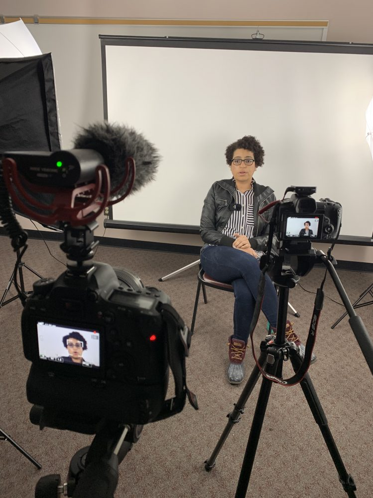 SSC Assistant Professor of the Arts Program, Lynette Atchley, sits in front of a white backdrop with two cameras focused on her during an interview shot for one of the schools digital media projects.