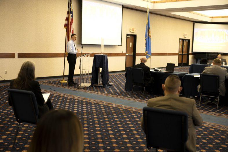 Man speaks to board meeting attendees.