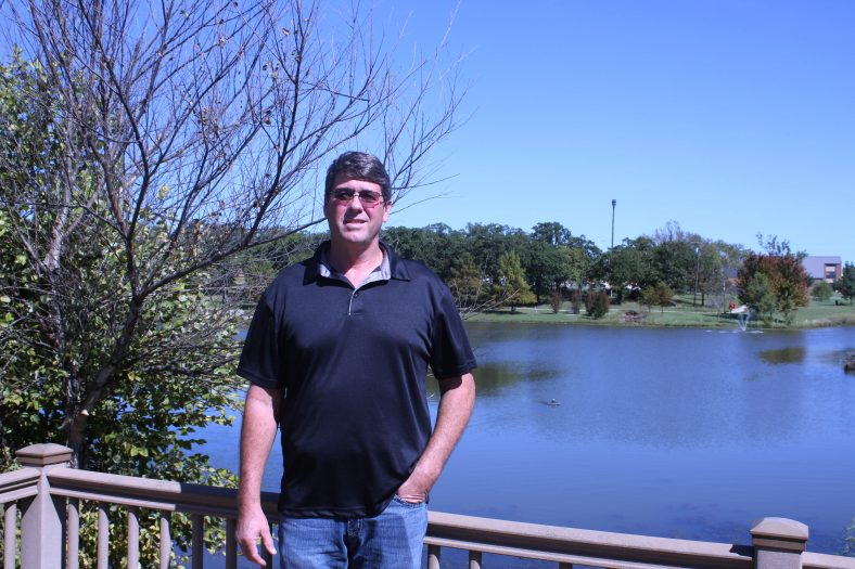 Director of Physical Plant and Campus Safety stands by campus pond.